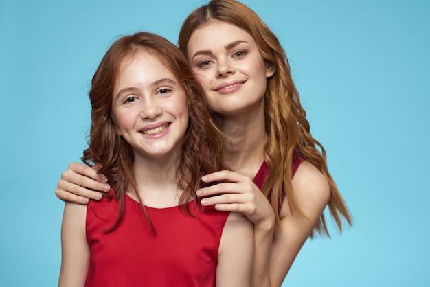 Mamma e figlia in abiti rossi intrattenimento lifestyle divertente studio sfondo blu