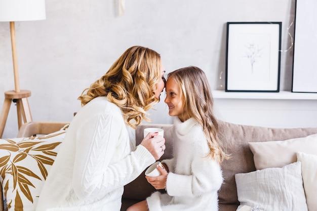 Mamma e figlia seduti sul divano in chat