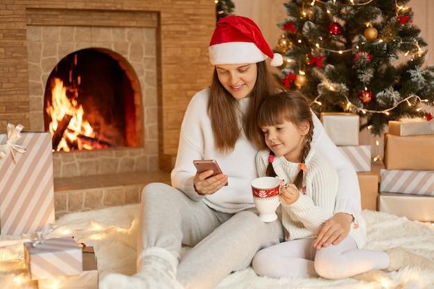 Mamma e figlia seduti vicino all'albero di natale, abbracciati, comunicano tramite videochiamata, divertendosi.