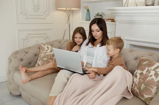 Figlia e figlio della mamma giocano sul computer portatile. ricreazione e svago della famiglia