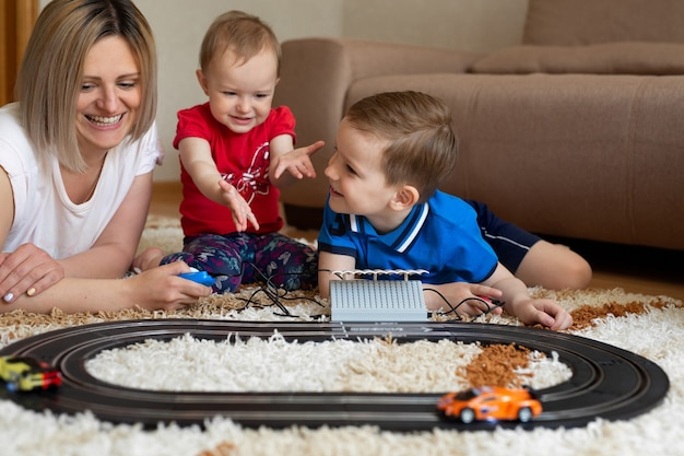 Mamma, figlia e figlio giocano a correre sul tappeto.
