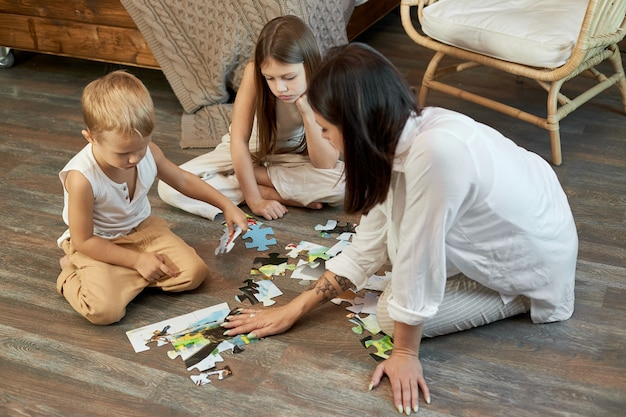 Mamma, figlia e figlio hanno messo insieme il puzzle sul pavimento. intrattenimento per la famiglia. ragazzo e ragazza donna giocano insieme