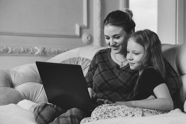 Mamma e figlia trascorrono del tempo insieme al laptop a casa in soggiorno sul divano. felice mamma e figlia caucasiche che usano il computer ridendo, navigando in internet, facendo acquisti online, guardando film cinematografici