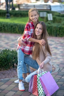 Mamma e figlia che camminano lungo la strada con le borse della spesa