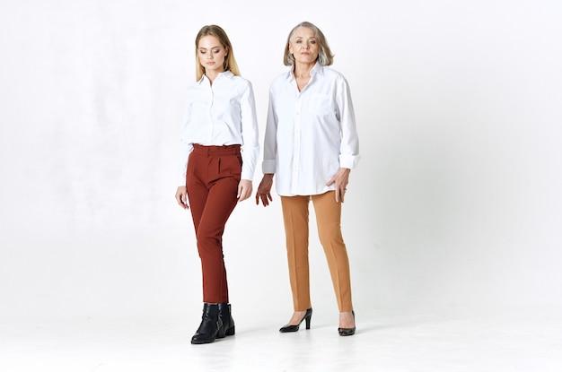 Mamma e figlia in camicie bianche sono in piedi accanto a uno stile di vita divertente in famiglia