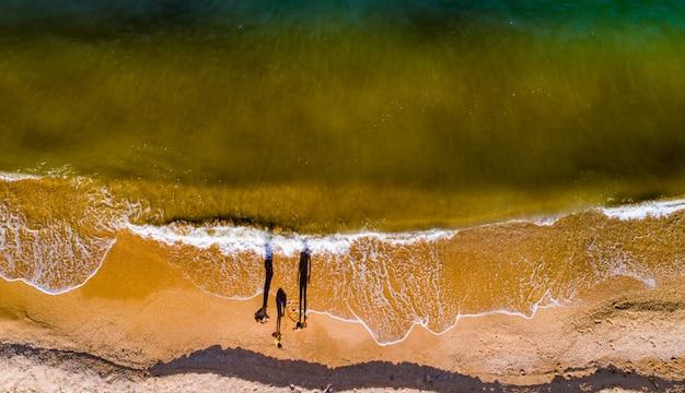 Mamma e figlie camminano tra le onde lungo la riva del mare