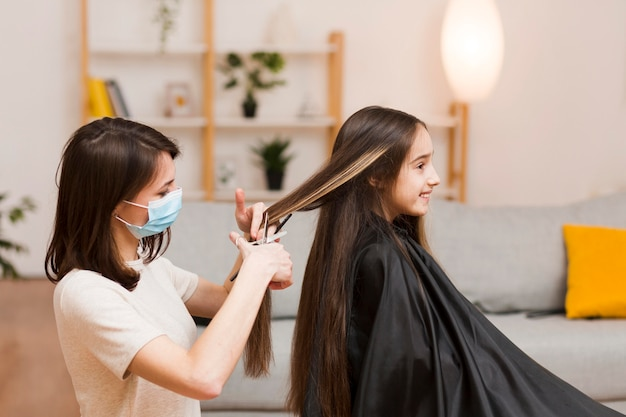Mamma che fa taglio di capelli ragazza