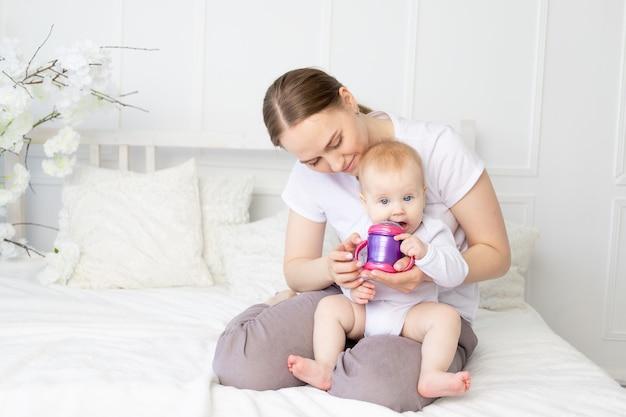 La mamma beve o allatta con il biberon un bambino su un letto bianco a casa, concetto di alimenti per bambini