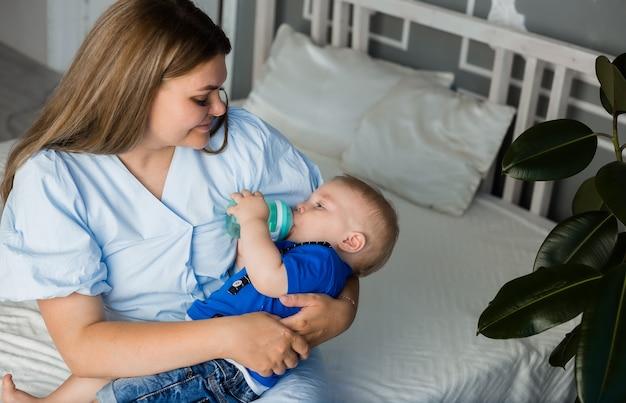La mamma dà da mangiare a un bambino con un biberon sul letto in camera