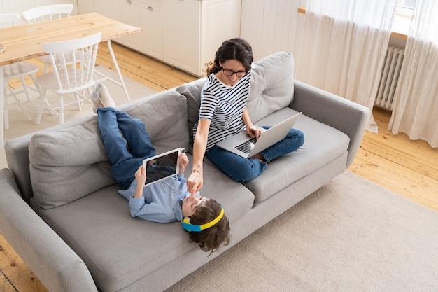 Lavoro a distanza libero professionista della mamma dall'ufficio domestico sul computer portatile si siede sul bambino del divano che gioca sul blocco del tablet
