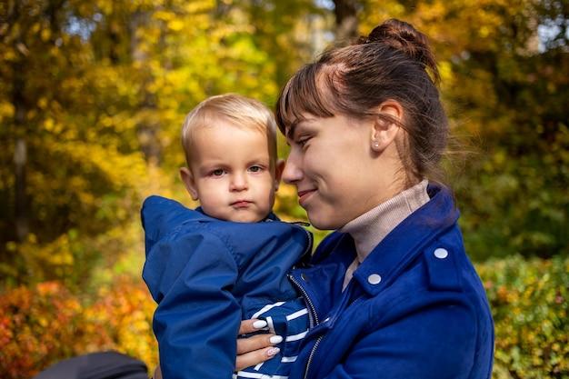 La mamma abbraccia dolcemente il bambino il bambino guarda la telecamera seriamente e severamente diverso