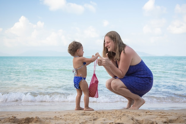 La mamma regala a suo figlio una borsa a rete sulla spiaggia cultura dell'ecologia fin dalla tenera età