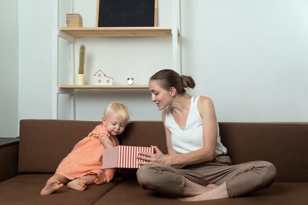La mamma dà la confezione regalo della sua piccola figlia. mamma e bambino guardano in una scatola aperta. . vacanza.