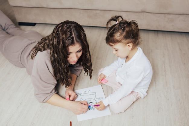 Mamma aiuta la figlia a disegnare con le matite colorate sul pavimento