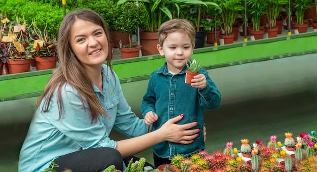 La mamma e il suo bambino in un negozio di piante guardando i cactus. giardinaggio in serra. giardino botanico, floricoltura, concetto di industria orticola