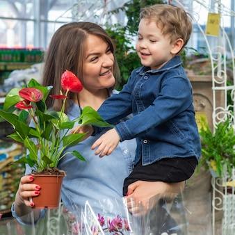 La mamma e il suo bambino in un negozio di piante guardando il fiore. giardinaggio in serra. giardino botanico, floricoltura, concetto di industria orticola