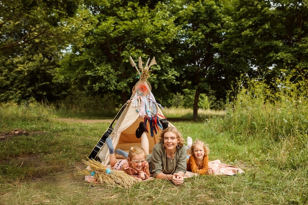 La mamma e le sue figlie trascorrono del tempo all'aperto in estate nella foresta, accanto al wigwam, decorazione del teepee.