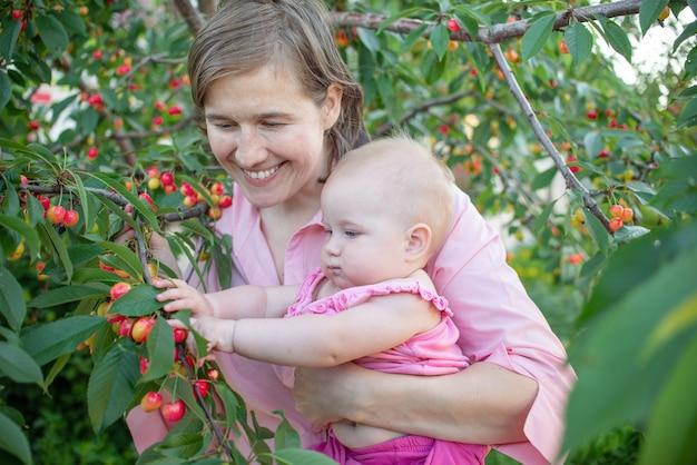 Mamma e la sua piccola figlia stanno raccogliendo ciliegie in una fattoria di frutta ridono e si divertono