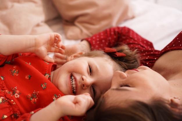 La mamma e la sua piccola figlia sono sdraiate sul letto una di fronte all'altra e sono felici