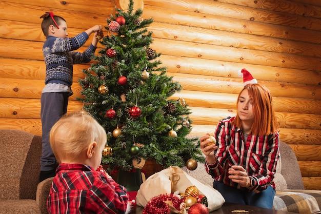 I sogni di mamma e figlio stanno decorando l'albero di natale
