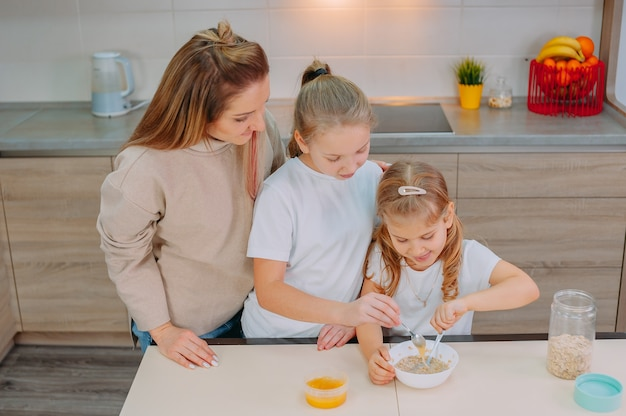 Una mamma e le sue due figlie aggiungono il miele alla farina d'avena in cucina.