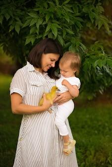 La mamma tiene il bambino in braccio e gioca con un'anatra, primavera, giornata calda, estate fuori