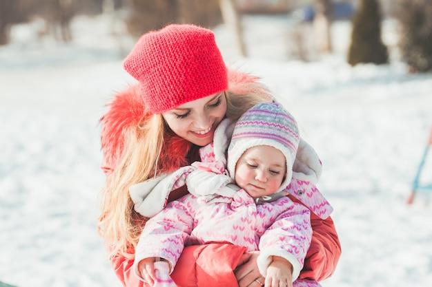 Mamma che abbraccia sua figlia mentre cammina in una giornata di sole invernale