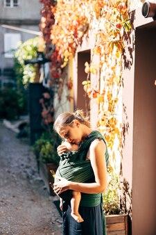 La mamma abbraccia il bambino in una fascia vicino al muro della casa intrecciata con l'edera