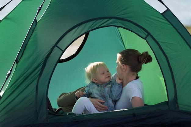 La mamma abbraccia il bambino mentre giace in tenda. riposo in campeggio. turismo, viaggi, attività all'aria aperta.