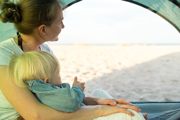 La mamma abbraccia il bambino mentre è seduta nella tenda turistica. vista mare e spiaggia dalla tenda da campeggio.