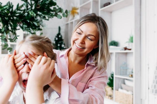 La mamma abbraccia sua figlia e si copre gli occhi da dietro Foto Premium