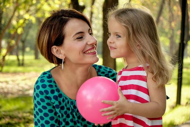 La mamma abbraccia una bambina che tiene un pallone nel parco