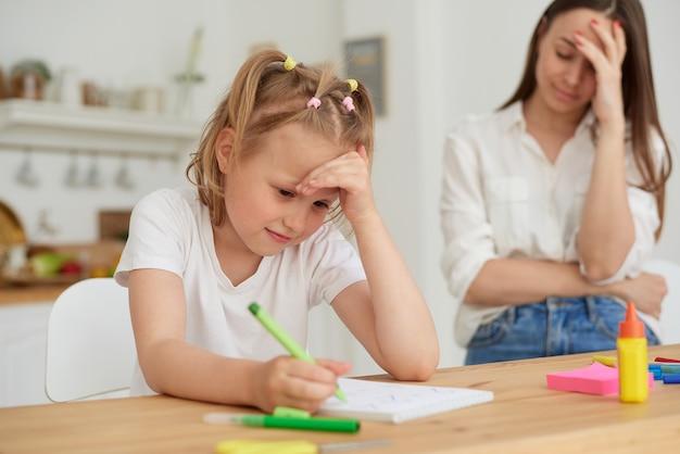 La mamma è arrabbiata perché sua figlia non vuole fare i compiti. genitori che insegnano ai bambini a casa, istruzione scolastica a casa, madre che aiuta sua figlia a fare i compiti, stress emotivo.