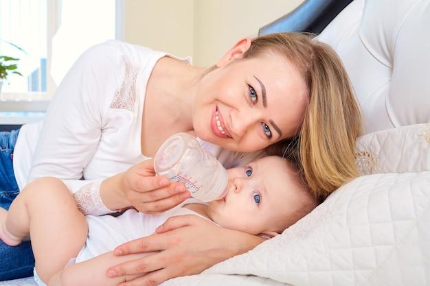 La mamma sta allattando il suo bambino da una bottiglia a letto con il cibo