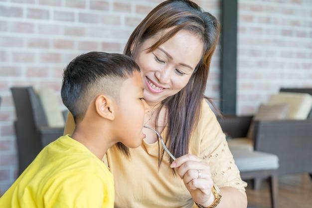 La mamma sta dando da mangiare a suo figlio con un sorriso.