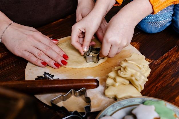 Mamma e bambino cuociono i biscotti in cucina e decorano i biscotti