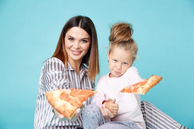 Mamma e bambino che mangiano pizza insieme al mattino.