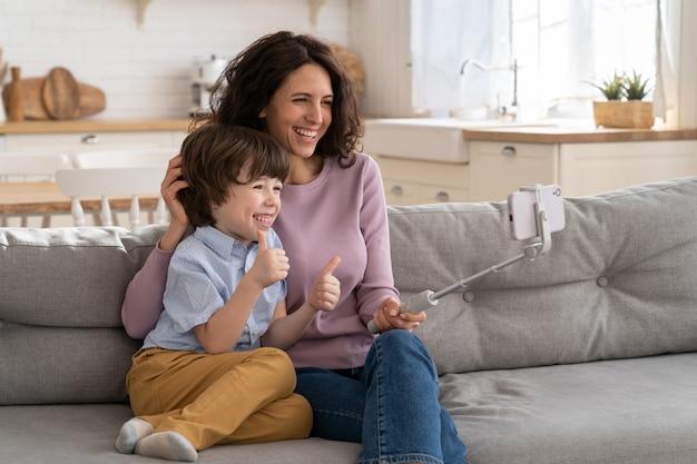 Mamma e bambino che mostrano come gesto tenendo il telefono sul selfie stick per la videochiamata si siedono sul divano di casa