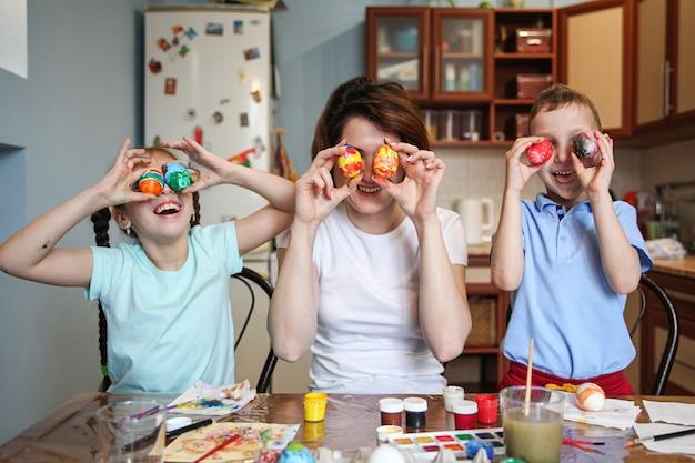 Mamma e bambini scherzano provando uova di pasqua dipinte come occhi a casa in cucina
