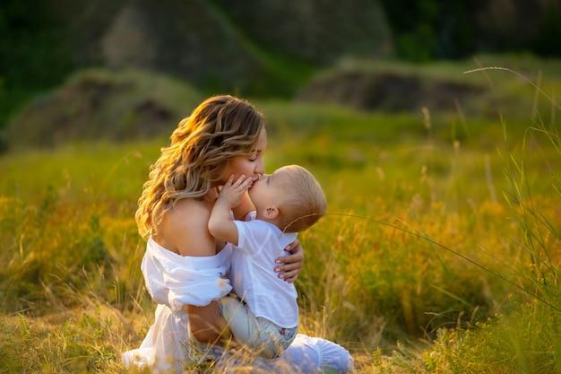 La mamma bacia suo figlio. festa della mamma. madre e figlio. il bambino bacia la madre. donna in un campo con un bambino. giornata della protezione dei bambini. bella natura con le persone