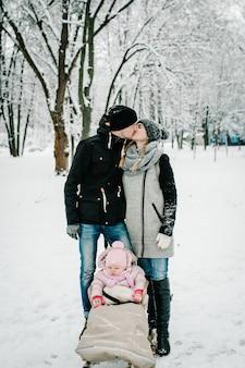 Mamma che bacia papà e figlia stanno all'aperto sullo sfondo inverno.