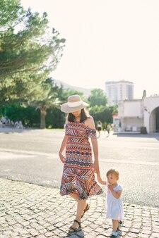 La mamma conduce una bambina per mano attraverso la piazza acciottolata
