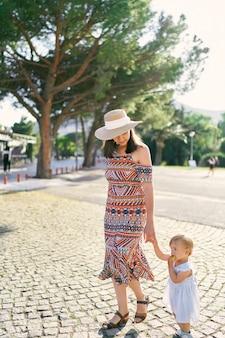 La mamma conduce una bambina per mano attraverso la strada acciottolata