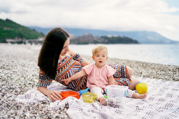 La mamma giace accanto a una bambina seduta su una coperta su una spiaggia di ciottoli