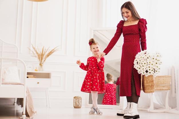 Mamma e figlia in abiti rossi in una luminosa camera da letto in stile scandinavo. famiglia felice. la mamma tiene un mazzo di margherite - foto di primavera