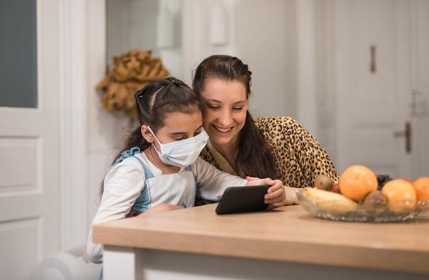 La mamma e la piccola figlia che utilizzano lo smartphone trascorrono del tempo in internet guardando i video clip online godendosi la musica preferita, le app utenti tecnologici moderni e l'attività con il concetto di bambino a casa.