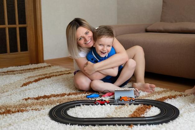 Mamma e figlio giocano a correre sul tappeto di casa, si divertono e si coccolano.
