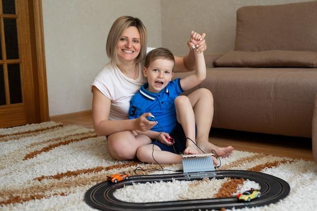 Mamma e figlio giocano a correre sul tappeto di casa.