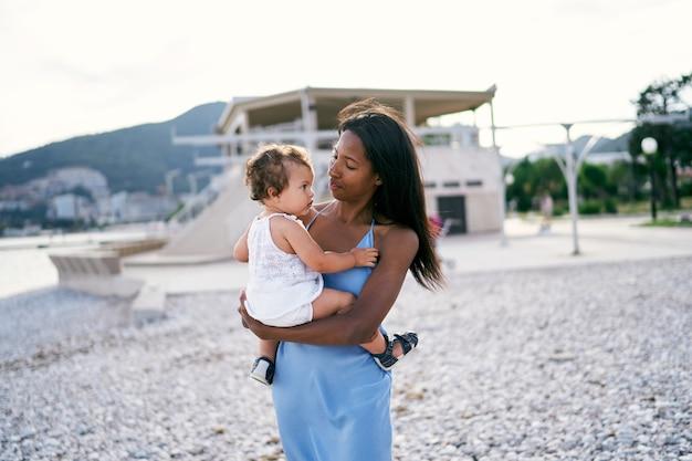 La mamma guarda la bambina seduta tra le sue braccia