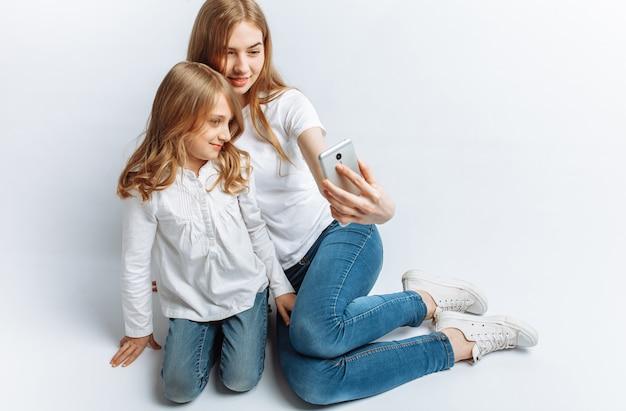 La mamma o la sorella maggiore fanno selfie bambina, famiglia felice